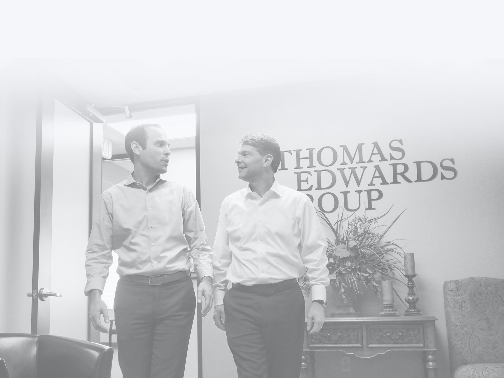 two professional men walking and talking in front of thomas edwards sign in office setting